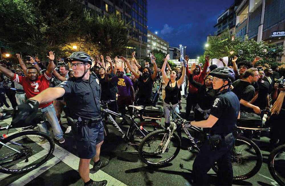 Charlotte police officers patrol on bicycles as people peacefully protest the killing of Keith Scott by a law enforcement officer. AP Photo