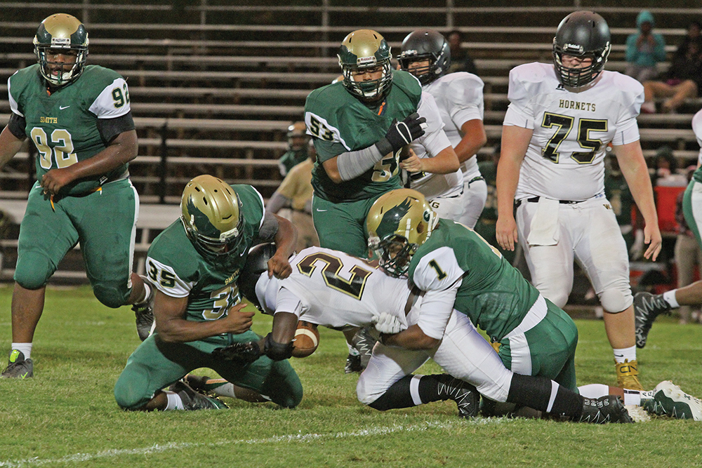 Western Guilford's Josh Mobley (#22) fumbles after being tackled by Smith linebackers Alex Moore (#1) and Downey Richmond (#35) in the second quarter of play. Photo by Joe Daniels/Carolina Peacemaker