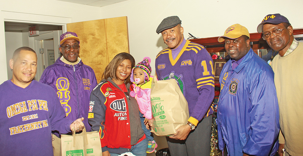 Omega Psi Phi Fraternity members: Michael Godetter, Lennitt Bligen, Gerry McCants, Basileus, Melvin Gass Jr, social action chair and Nate Tollison bring cheer to Tamara Cuthbertson and 2-year-old Tayana. Photos by Charles Edgerton/Carolina Peacemaker