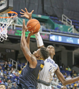 Aggie junior forward Davaris McGowens has his shot blocked by UNCG's James Dickey.  McGowens led the Aggies with 19 points and 10 rebounds. Photo by Joe Daniels/Carolina Peacemaker