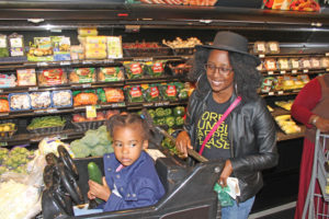 Shayla Rhem and her daughter, Journee, joined the Cash Mob and shopped at the Renaissance Community Co-op.  Photo by  Charles Edgerton/Carolina Peacemaker