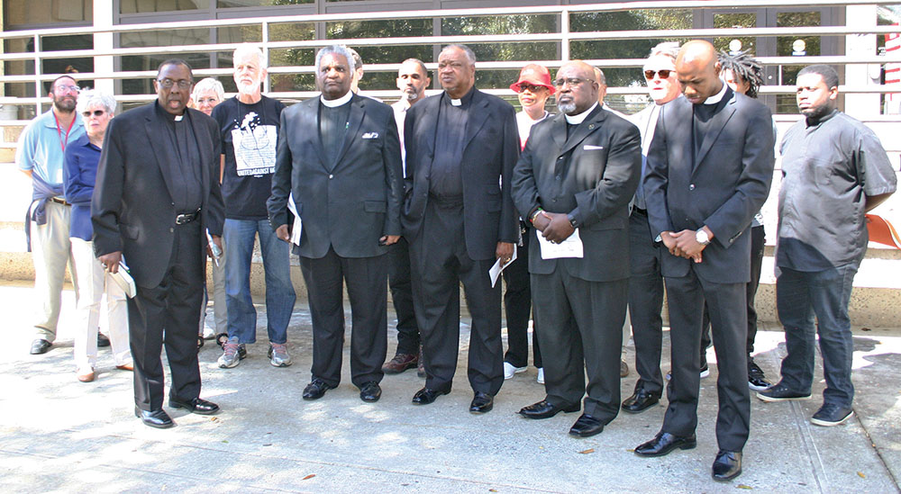 Greensboro pastors and supporters of Jose Charles gather outside the Guilford County Courthouse in downtown Greensboro on April 4. Pastors Nelson Johnson, Ezekiel Ben Israel, Cardes Brown, Daran Mitchell, Randal Keeney and Bradley Hunt. Photo by Yasmine Regester/Carolina Peacemaker
