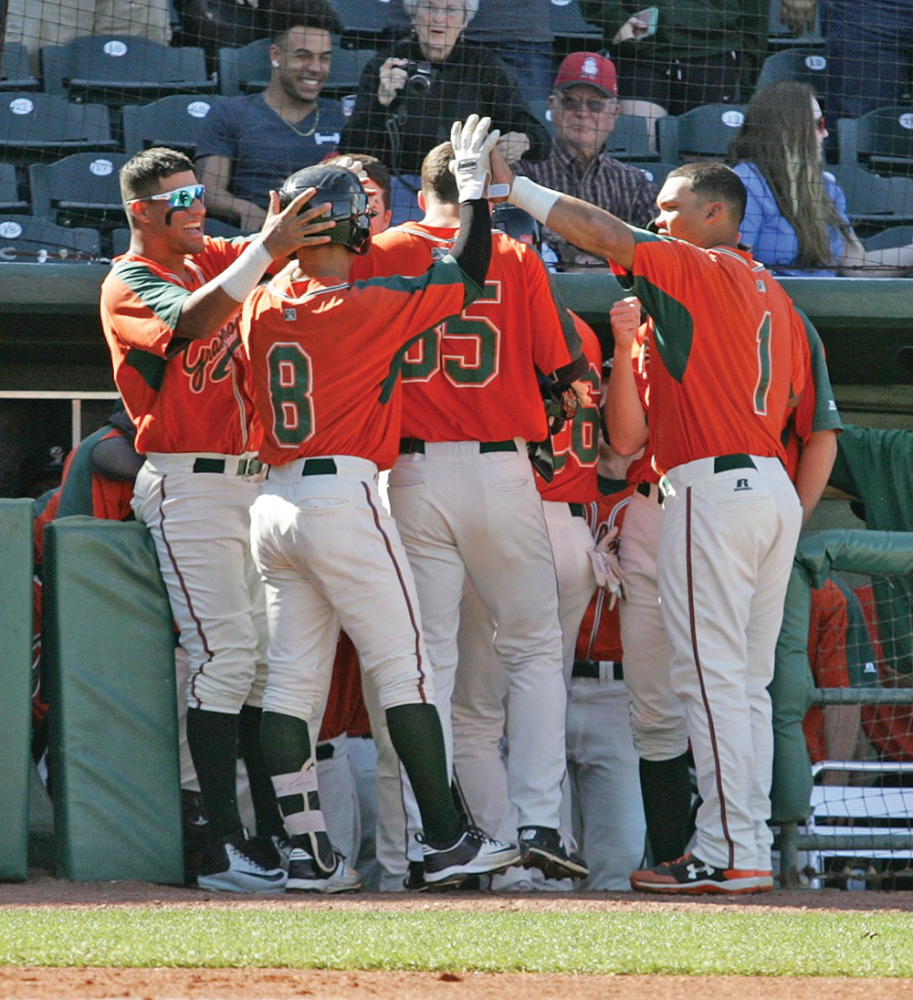 Greensboro Hopper Luis Pintor is congratulated after hitting a grand-slam in the second inning. Photo by Joe Daniels/Carolina Peacemaker