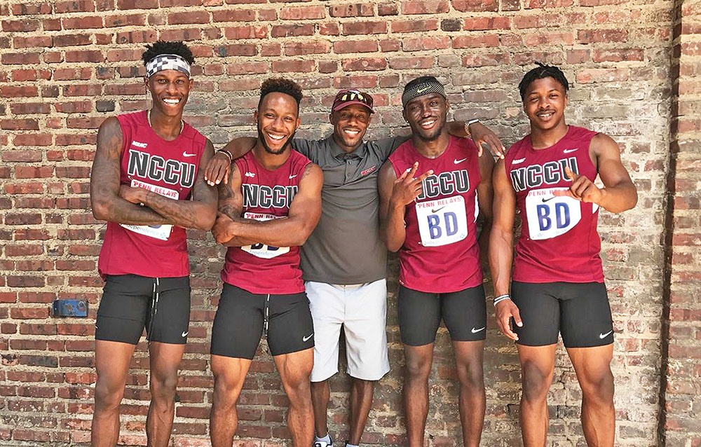 """The NCCU 4x100-meter relay team of Deontae Williams, Jonathan Williams, Blake Hartsfield and Isaac Roberts celebrate a runner-up finish at the Penn Relays with head coach Tavius """"T.J."""" Walker (middle). Photo courtesy NCCU"""