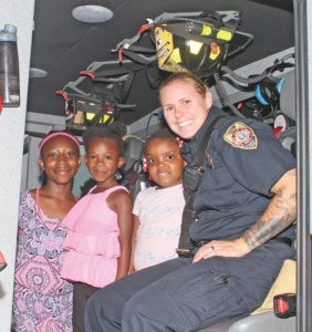 Greensboro firefighter Jessica Clark talks to little Willow Oaks residents (L-R) Shaniya Love, Summer Rogers and Jala Williams at the Willow Oaks National Night Out.
