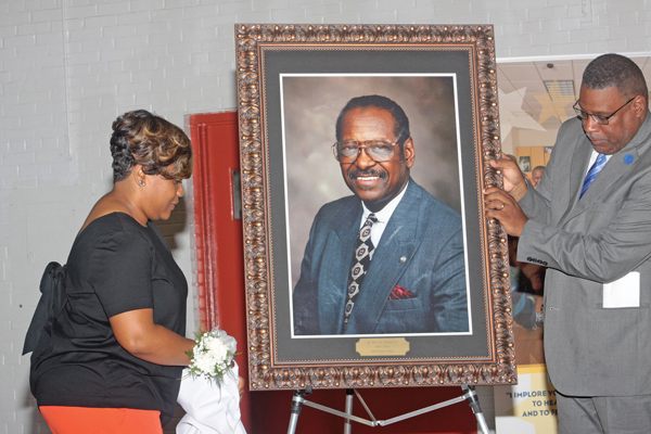 Leah Swann, granddaughter of the late Dr. Melvin C. Swan Jr., unveils a portrait of her late grandfather with David Miller (former principal of Aycock Middle School, now renamed Swann Middle School). Photo by Charles Edgerton/Carolina Peacemaker