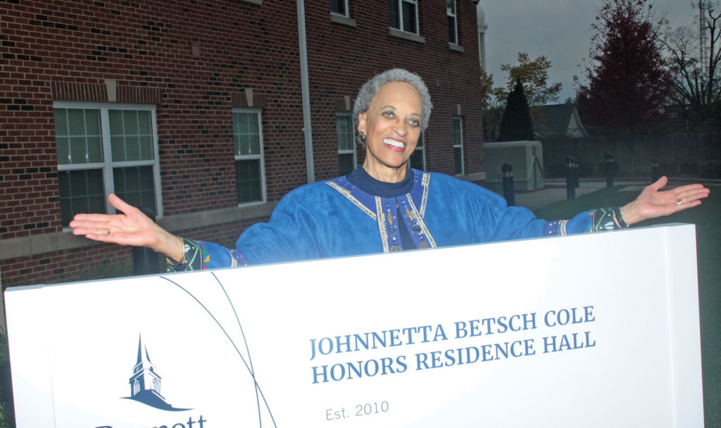 Dr. Cole stands behind a sign at the Bennett residence hall named in her honor.