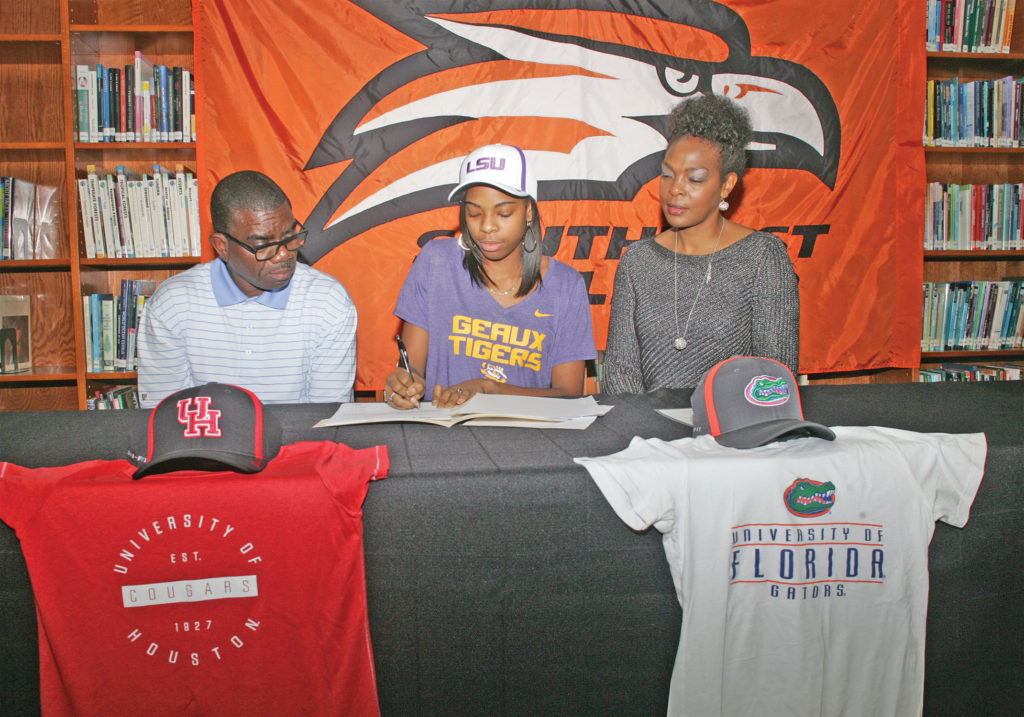 With her parents, Evans and Sherren Oviosun at her side, Kiya Oviosun signs a letter of intent to attend LSU on a track scholarship.  Photo by Joe Daniels.