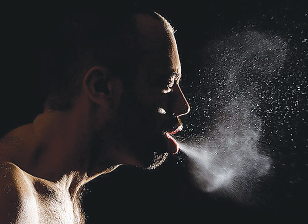 Cover up when sneezing. The flu is transmitted from person to person through the air in small aerosolized droplets and can spread when an infected person  talking, coughing and sneezing.